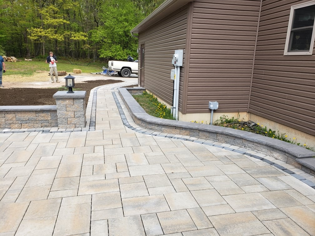 finished walkway around the house with black brick detailing