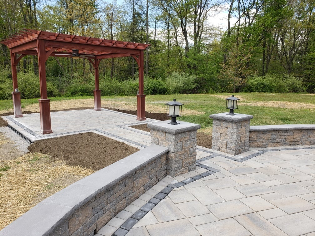 completed patio with red wood shade roof and pathway lit by lanturns