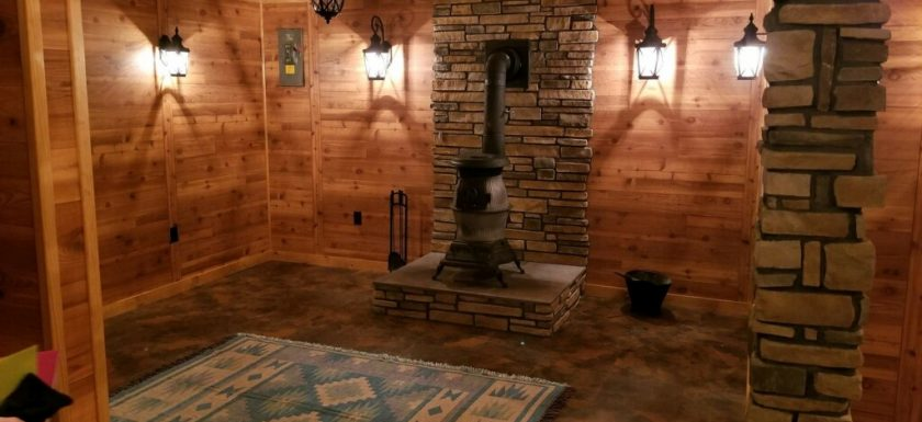 authentic wood walls and ceiling with stone pillar and wood stove heating